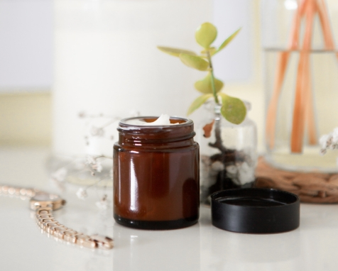 cream in jar on a table with a plant beside it